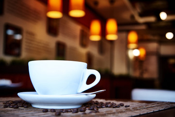 White cup with a spoon on a saucer on a bamboo napkin with scattered coffee beans.