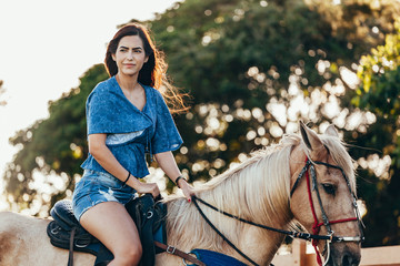 Young woman riding horse on the countryside