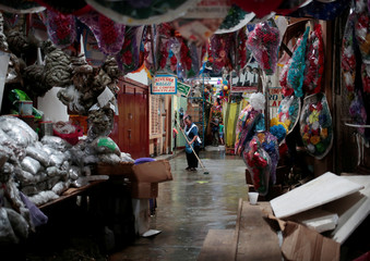 A merchant sweeps inside of the Roberto Huembes market during National strike in Managua