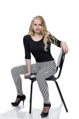 young blonde girl posing on chair.