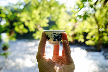 Small chinese porcelain cup in front of water and green leaves bokeh background