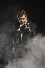 Handsome middle aged man gangster with Thompson machine gun on dark background