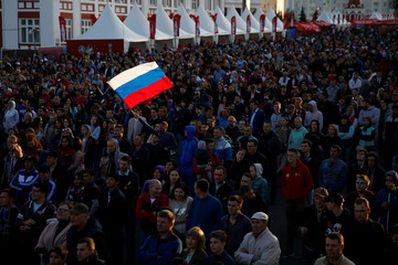 Fans wave a Russian flag as they watch the Soccer World Cup match between Russia and Saudi Arabia at the FIFA Fan Fest in Saransk