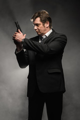Handsome middle aged detective man with gun on dark background
