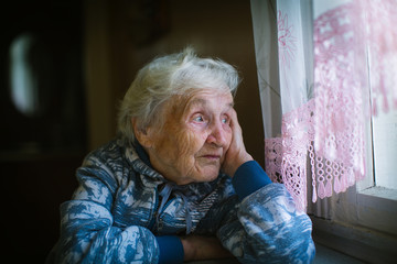 An elderly pensioner woman looks out the window sadly.