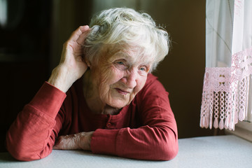 An elderly woman listens with her hand to her ear. Hard of hearing, seniors hearing loss.