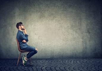 Pensive man sitting against gray