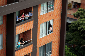 People look on as Bonavento building is imploded in Medellin