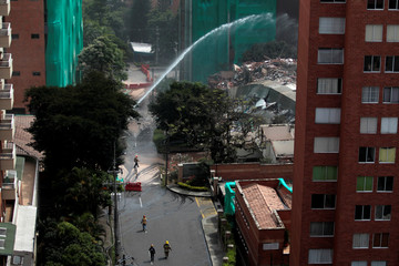 Firefighters work in the site of the implosion of Bonavento building in Medellin