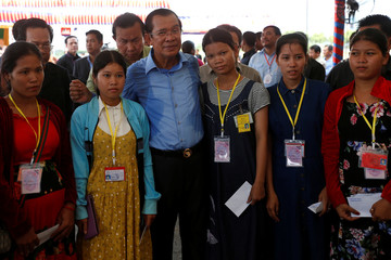 Cambodia's Prime Minister Hun Sen poses after delivering envelops to garment workers during a rally in Kandal province