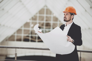 Photo of male architect in red hardhat holding blueprints