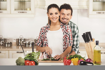 Lovely couple preparing healthy meal in kitchen.