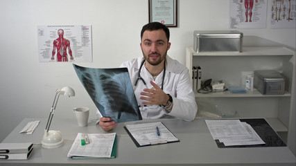 Medical doctor friendly speaking to camera holding x-ray