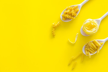 Different pasta types. Fusilli, penne, fettuccine in spoons on yellow background top view copy space
