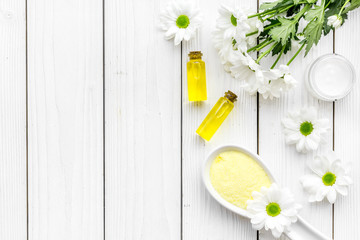 Cosmetics for skin care with chamomile. Chamomile oil, cream, spa salt on white wooden background top view copy space