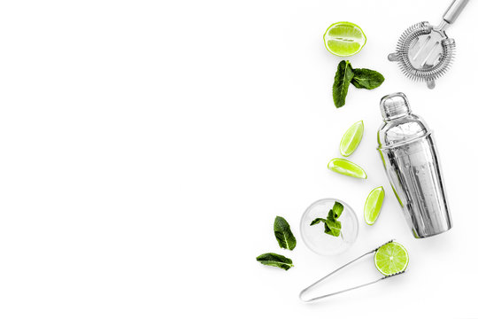 Process of making mojito concept. Ingredients and crockery. Slices of lime, mint, glass with ice cubes, shaker, strainer on white background top view copy space