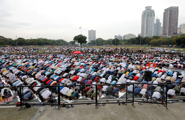 Filipino Muslims take part in morning prayers during the first day celebration of Eid al Fitr at Luneta Park in Manila