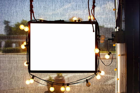 Blank hanging sign surrounded by party lights in shop window with semi-transparent dark solar shades behind and dimly viewed city street outside