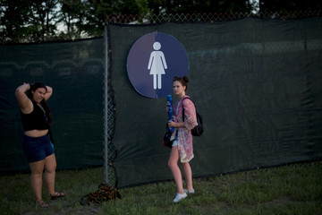 Amber Wilson, 20, holds beer cans while her friends use the portable restroom during the Firefly Music Festival in Dover, Delaware U.S.