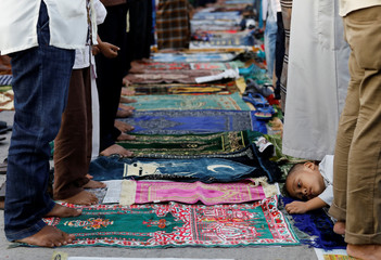 A boy is seen during prayers to celebrate Eid al-Fitr, marking the end of the holy fasting month of Ramadan, at Sunda Kelapa port in Jakarta