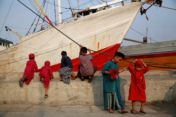Children play after attending prayers to celebrate Eid al-Fitr, marking the end of the Muslim holy fasting month of Ramadan, at Sunda Kelapa port in Jakarta,