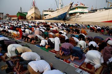 Muslims attend prayers to celebrate Eid al-Fitr, marking the end of the holy fasting month of Ramadan, at Sunda Kelapa port in Jakarta,