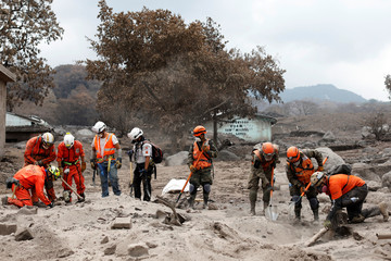Rescue workers search for missing families at the area affected by the Fuego volcano at San Miguel Los Lotes in Escuintla,