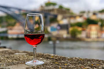 Glass of port wine on an old stone wall at an outdoor restaurant with the Douro river  and Dom Luis I bridge blurred in the background in Porto, Portugal