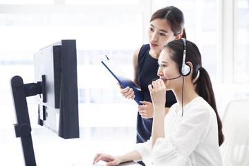 コールセンターで先輩の指導を受ける女性会社員