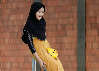 A Muslim girl plays before morning prayers during the first day celebration of Eid al Fitr at a mosque in Bangkok
