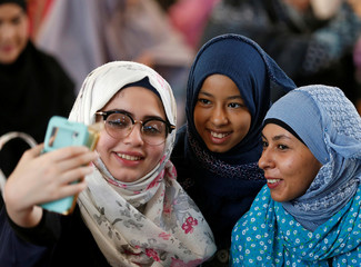 Muslim women take a selfie before morning prayers during the first day celebration of Eid al Fitr at a mosque in Bangkok