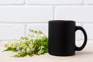 Black coffee mug mockup with white spiraea flowers