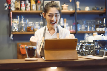 Attractive young beautiful caucasian barista standing on counter bar celebrate success looking at tablet in coffee shop.Successful corporate, winners excited of victory