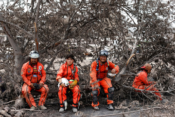 "Members of the Mexican rescue team, known as ""the Topos"", rest at the area affected by the Fuego volcano at San Miguel Los Lotes in Escuintla,"