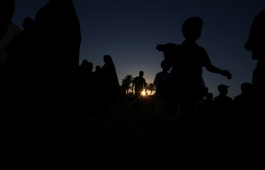 Palestinians arrive to attend Eid al-Fitr prayers in Khan Younis in the southern Gaza Strip