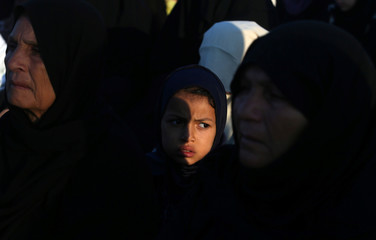 Palestinian girl looks on as she attends Eid al-Fitr prayers in Khan Younis in the southern Gaza Strip