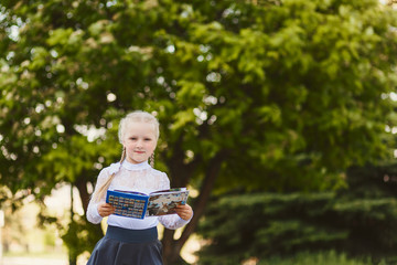 beautiful little girl seven years old with pigtails in a school uniform outdoors