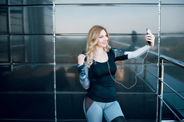 Fitness woman standing in balcony and using mobile phone.