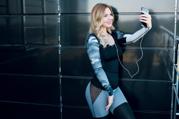 Woman using a smartphone to take a selfie photo after doing a workout.