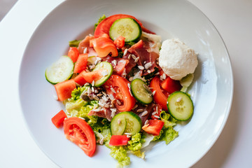 Plate of salad with tomatoes, cucumber, bell pepper, cream cheese, ham on the white table. Glass of iced water with mint and lemon.