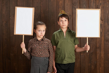 Children are dressed in retro military uniforms. They're holding blank posters for veterans portraits.