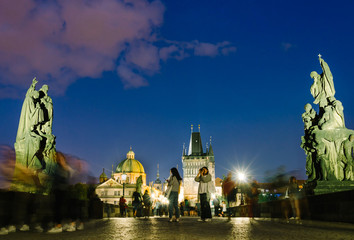 Tourists strolling and take photographs on the Charles bridge at evening