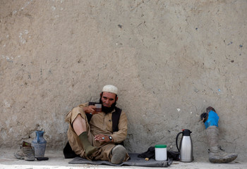A disabled Afghan man drinks tea while sitting by the roadside on the first day of the Muslim holiday of Eid al-Fitr, which marks the end of the holy month of Ramadan, in Kabul, Afghanistan