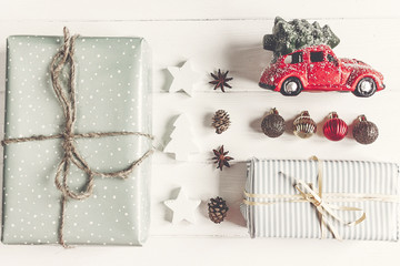 merry christmas concept, flat lay. modern presents with car carrying tree, ornaments  on rustic white wood top view. seasonal greetings. happy holidays. xmas card, instagram blogging