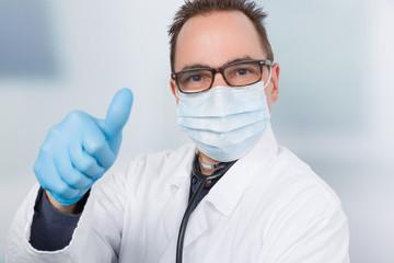 Ein Arzt mit medizinischen Handschuhen und Mundschutz zeigt Daumen hoch