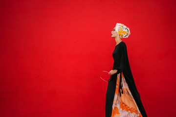 Portrait of a fashionable Muslim woman model in a head scarf hijab against a red background in a studio.