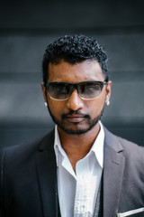 Professional portrait head shot of a handsome young Indian man in a 3 piece suit during the day.