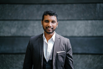 Professional portrait head shot of a handsome young Indian man in a 3 piece suit during the day. He is smiling.