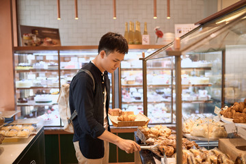 Handsome asian man choosing bakery in store