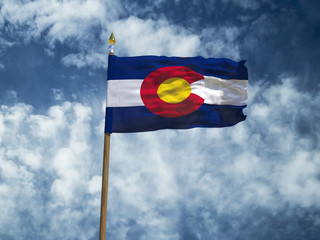 Colorado flag USA flag Silk waving flag made transparent fabric of Colorado US state with wooden flagpole gold spear on background sunny blue sky white smoke clouds real retro photo 3d illustration